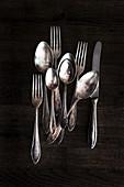 Silver cutlery on a dark wooden background