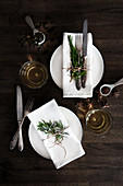 Two place settings with cloth napkins, vintage cutlery and a rosemary sprig on a dark wooden table