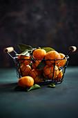 Tangerines in basket on dark