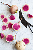 Sliced and whole watermelon radishes on a marble countertop with