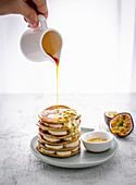 Oat pancakes with bananas, passionfruit and maple syrup