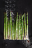 Raw green asparagus spears with sea salt and red pepper berries
