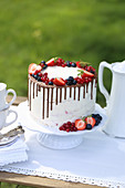White cake with fresh berries on garden table