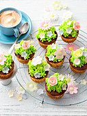 Chocolate cupcakes with green icing and fondant flowers
