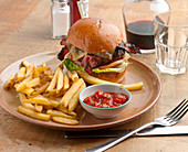 Burger and chips - Beef pattie with bacon, melted cheese and salad, in a brioche bun