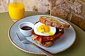 Bacon and fried egg sandwich, with white crusty bread and brown sauce