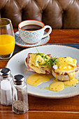 Eggs Benedict breakfast - Two poached eggs on muffins, with ham and hollandaise sauce