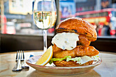 Battered fish in a brioche bun with lettuce and tartare sauce
