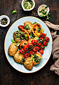 Hasselback potatoes with pesto and baked tomatoes