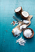 Still life with halved coconut, desiccated coconut, and coconut shavings