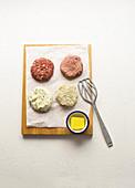 Raw burgers made from lamb, ground beef, cauliflower, and fish