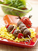 meatball skewers on saffron rice with grilled tomatoes and lettuce