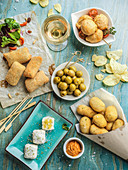 Different croquettes served with olives and wine