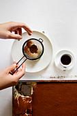 Dusting creamy tiramisu with cocoa