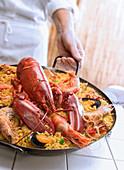 Koch serviert Paella mit Hummer