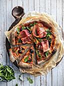 Prosciutto pizza with arugula and olives