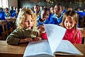 European girls visiting a school, Kamba County, Kenya