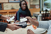 Close-up of woman paying waitress with contactless card
