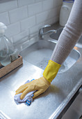 Woman in rubber glove cleaning kitchen counter