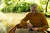 Happy man fly fishing in a boat