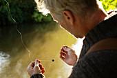Man preparing fly fishing line at river