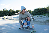 Young woman skateboarding on a beach path