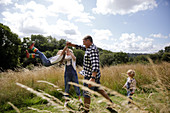 Happy family playing in sunny rural field