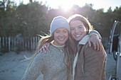 Happy young women friends hugging outdoors