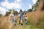 Happy family holding hands running in sunny rural field
