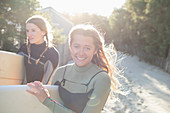 Happy young female surfers on sunny beach path