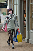 Young woman in face mask with shopping bags on sidewalk