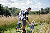 Family holding hands walking in sunny rural summer field