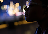 Young woman in stylish glasses at night