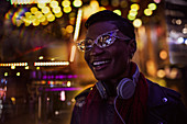 City lights around happy young woman in funky eyeglasses