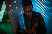 Young woman in face mask using smartphone in blue light