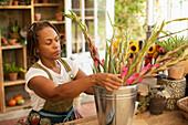 Female florist arranging flowers in bucket in shop owner