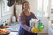 Smiling woman with cleaning supplies in kitchen