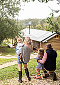 Parents and daughters looking at cabin from path in woods