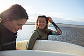 Happy young female surfers with surfboards on sunny beach