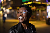 Happy young woman in funky glasses on city street at night