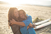 Happy young female surfers hugging on sunny beach