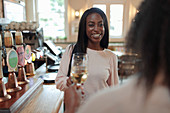 Happy young woman toasting wine glasses with friend in bar