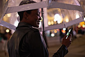 Happy young woman using smartphone under umbrella at night