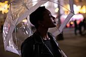 Young woman under umbrella on city sidewalk at night