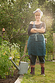 Confident woman with watering can in summer garden