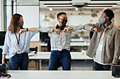 Happy business people in face masks bumping elbows in office