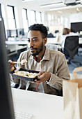 Businessman eating takeout sushi lunch at computer in office