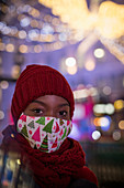 Young woman in christmas face mask in city at night
