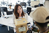 Businesswoman receiving packages from courier in office