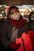 Young woman in Christmas facemask with shopping bags in taxi
